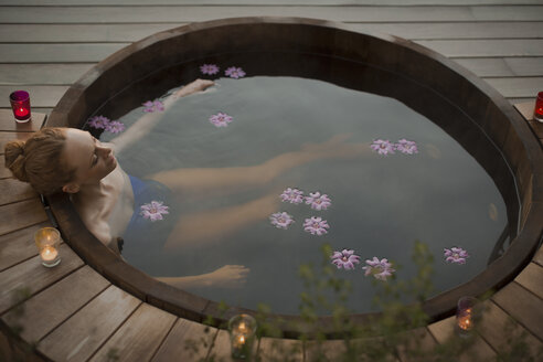 Serene woman soaking in hot tub with flowers and candles on patio - HOXF02695