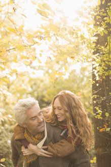 Affectionate couple piggybacking in autumn woods - HOXF02698