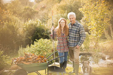 Portrait smiling couple with dog gardening raking leaves in autumn garden - HOXF02701