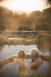 Serene affectionate couple soaking in hot tub on patio with autumn view - HOXF02704