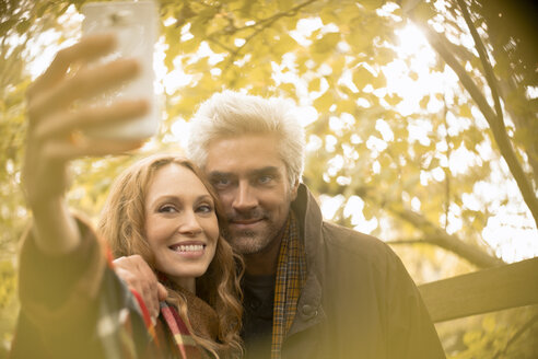 Smiling couple taking selfie with camera phone under autumn tree - HOXF02707