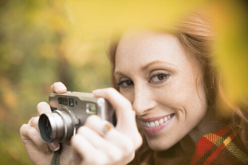 Close up smiling woman using digital camera among autumn leaves - HOXF02710