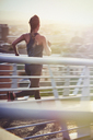 Female runner running on sunny urban footbridge at sunrise - HOXF02722