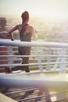 Female runner running on sunny urban footbridge at sunrise - HOXF02722