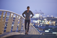 Female runner resting stretching legs on urban footbridge at dawn - HOXF02731