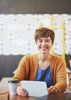 Portrait smiling businesswoman using digital tablet drinking coffee at cafe table - HOXF02734