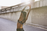 Fit female runner in sports bra stretching arms overhead on urban street - HOXF02740