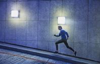 Male runner running ascending illuminated urban ramp - HOXF02743