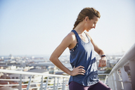 Female runner resting checking smart watch fitness tracker on sunny urban footbridge - HOXF02746
