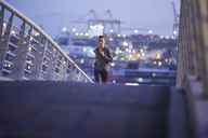 Female runner running on urban footbridge at dawn - HOXF02749