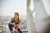 Female runner resting stretching leg and drinking water on sunny urban footbridge - HOXF02752