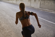 Fit female runner in sports bra and mp3 player armband running on urban street - HOXF02764