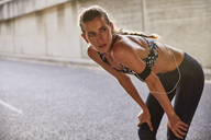 Tired fit female runner in sports bra with mp3 player armband resting on urban street - HOXF02773