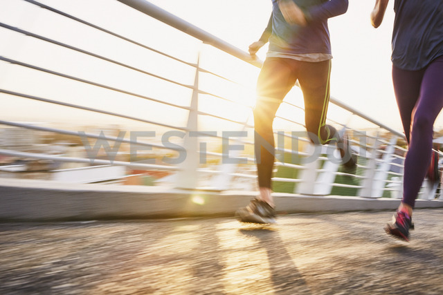 Runner couple running on sunny urban footbridge at sunrise - HOXF02782
