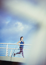 Female runner running on sunny footbridge - HOXF02794