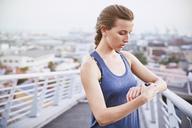 Female runner checking smart watch fitness tracker on urban footbridge - HOXF02809