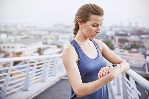 Female runner checking smart watch fitness tracker on urban footbridge - HOXF02809