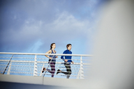 Runner couple running on sunny footbridge - HOXF02824