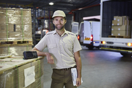 Portrait confident truck driver worker at distribution warehouse loading dock - HOXF02851