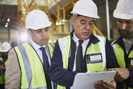 Managers with clipboard meeting in distribution warehouse - HOXF02860