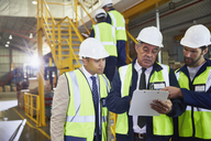 Manager and workers with clipboard meeting in distribution warehouse - HOXF02872