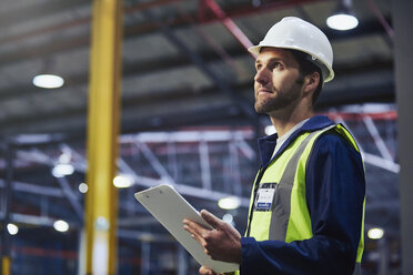 Worker with clipboard looking up in distribution warehouse - HOXF02881