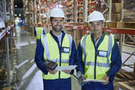 Portrait confident workers with scanners and clipboards in distribution warehouse - HOXF02887