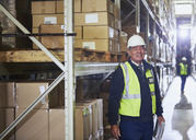 Portrait smiling manager with clipboard next to shelf in distribution warehouse - HOXF02893
