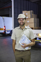 Portrait smiling truck driver worker with clipboard at distribution warehouse loading dock - HOXF02899