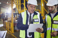 Manager and worker with clipboard meeting in distribution warehouse - HOXF02905