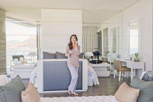 Woman talking on cell phone in modern luxury home showcase bedroom - HOXF02914