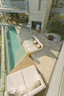 Sunny modern luxury home showcase patio with chaise lounges and lap pool - HOXF02917