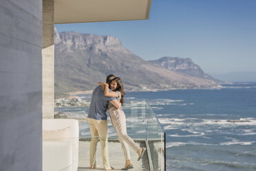 Couple hugging on sunny luxury balcony with ocean and mountain view - HOXF02923