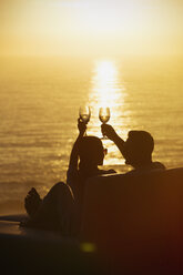 Silhouette couple toasting wine glasses on balcony with tranquil sunset ocean view - HOXF02929
