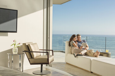 Couple using digital tablet on chaise lounge on sunny luxury balcony with ocean view - HOXF02938