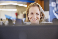 Portrait smiling businesswoman working at computer - HOXF02956