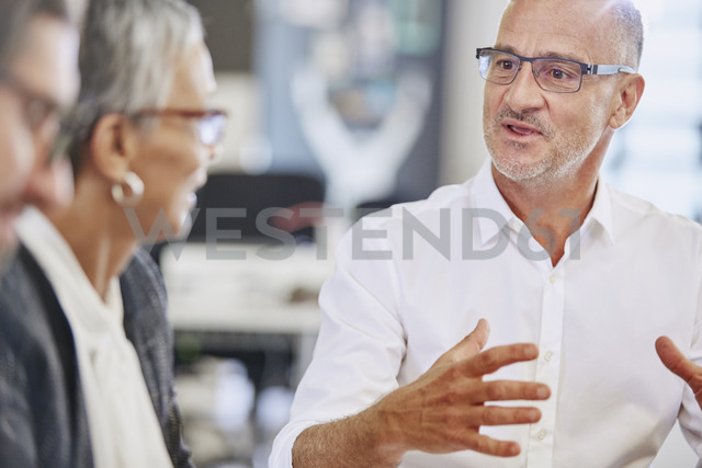 Businessman explaining to colleagues in meeting - HOXF02959