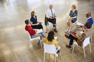 Business people talking in meeting circle - HOXF03004