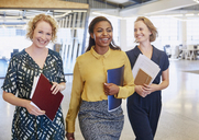 Smiling businesswomen walking in office - HOXF03052