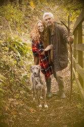 Portrait smiling couple with dog and walking stick along autumn fence - HOXF03088