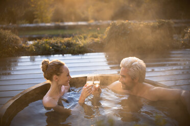 Couple toasting champagne glasses soaking in hot tub on autumn patio - HOXF03109