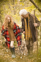 Couple with dog and walking stick in autumn woods - HOXF03115