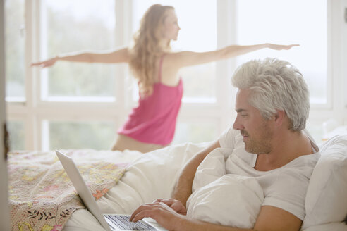 Woman practicing yoga warrior 2 pose in bedroom with husband using laptop in bed - HOXF03118