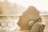 Serene man with headphones listening to music on sunny patio - HOXF03130