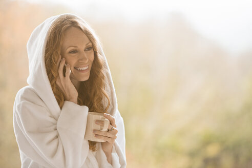 Smiling woman in hooded bathrobe talking on cell phone and drinking coffee - HOXF03133
