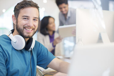 Portrait confident creative businessman with headphones working in office - HOXF03142