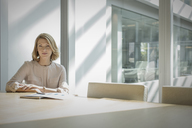 Portrait confident businesswoman sitting at sunny conference table - HOXF03205