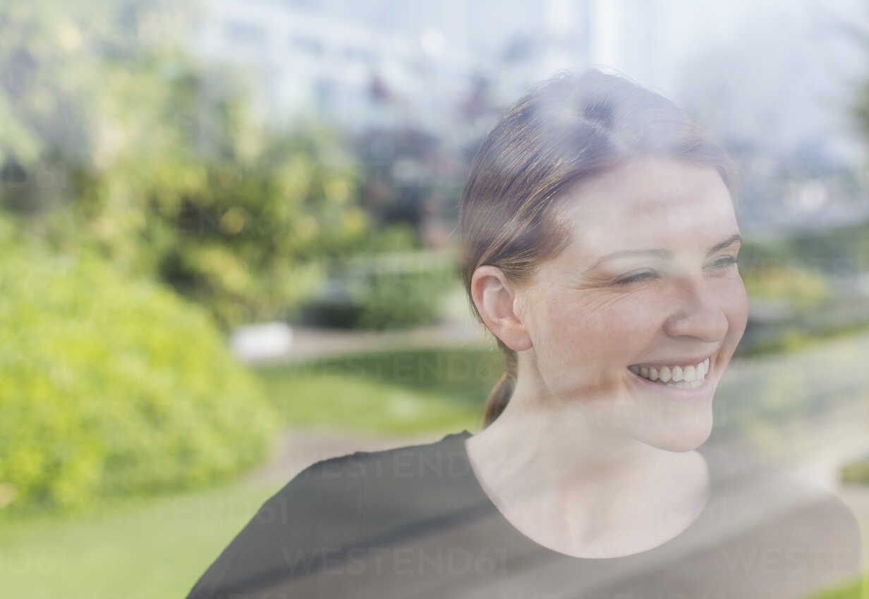 Smiling woman looking out window - HOXF03211 - Martin Barraud/Westend61