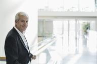 Portrait confident senior businessman in modern lobby - HOXF03217