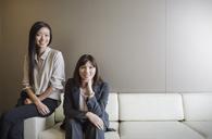 Portrait confident businesswomen on sofa - HOXF03220